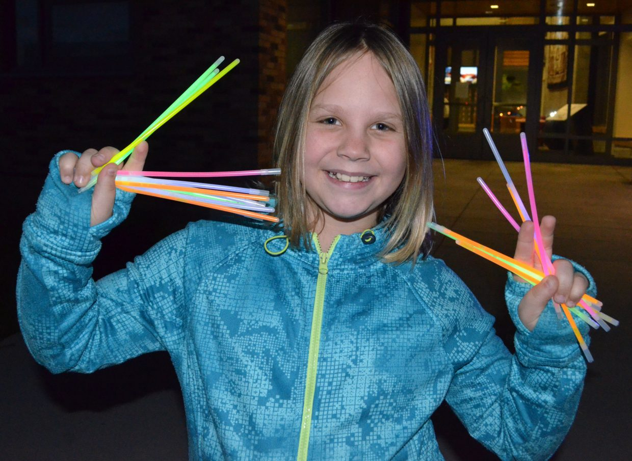 Caroline Schenck, 10, waves around handfuls of leftover glow sticks during The Memorial Hospital Glow Run 5K Saturday night. Runners adorned themselves with colorful items as the sun went down along the course.