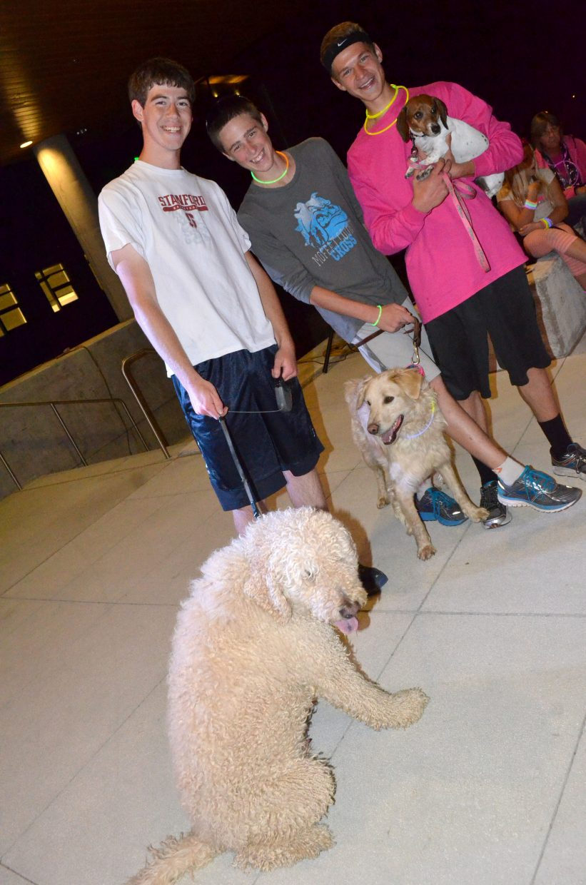 From left, Moffat County High School runners Nick Pugh, Brandon Beason and Garrett Flint cool down on the Colorado Northwestern Community College patio following The Memorial Hospital Glow Run 5K Saturday night. The three were among a number of runners who had canine companions run the course with them.