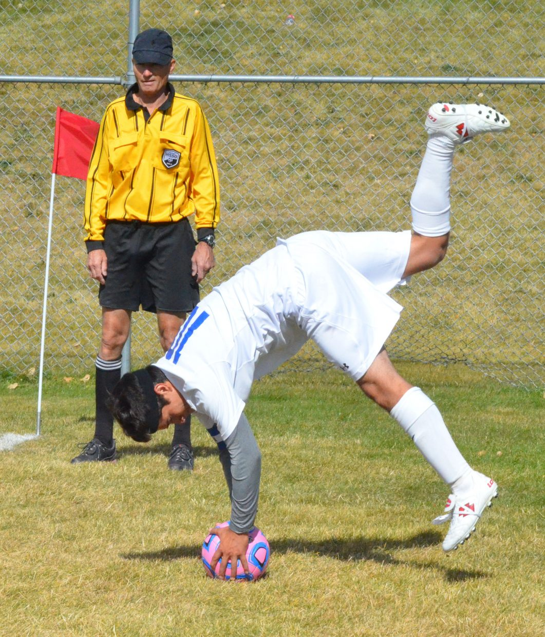 Moffat County High School's Ulises Silva goes into a handspring for a throw-in during Saturday's soccer game against Grand Valley.