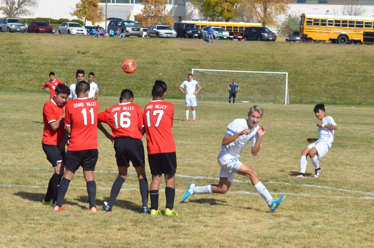 Moffat County High School's Wyatt Nielsen (19) gets clear as teammate Marco Hernandez takes a free kick during Saturday's soccer game against Grand Valley.