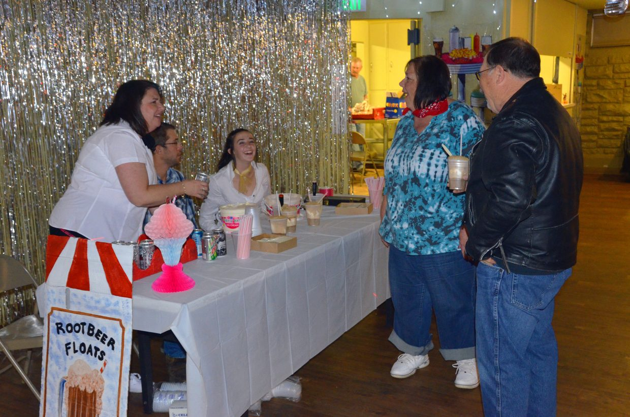 From left, volunteers Tammie Johannes, Kyle Reish and Erin Fagan provide root beer floats during the Sock Hop fundraiser for the Senior Social Center held Saturday night at the Moffat County Fairgrounds Pavilion. Foods like hot dogs, chips and other concessions provided aided in the money-raising process for the ongoing project.