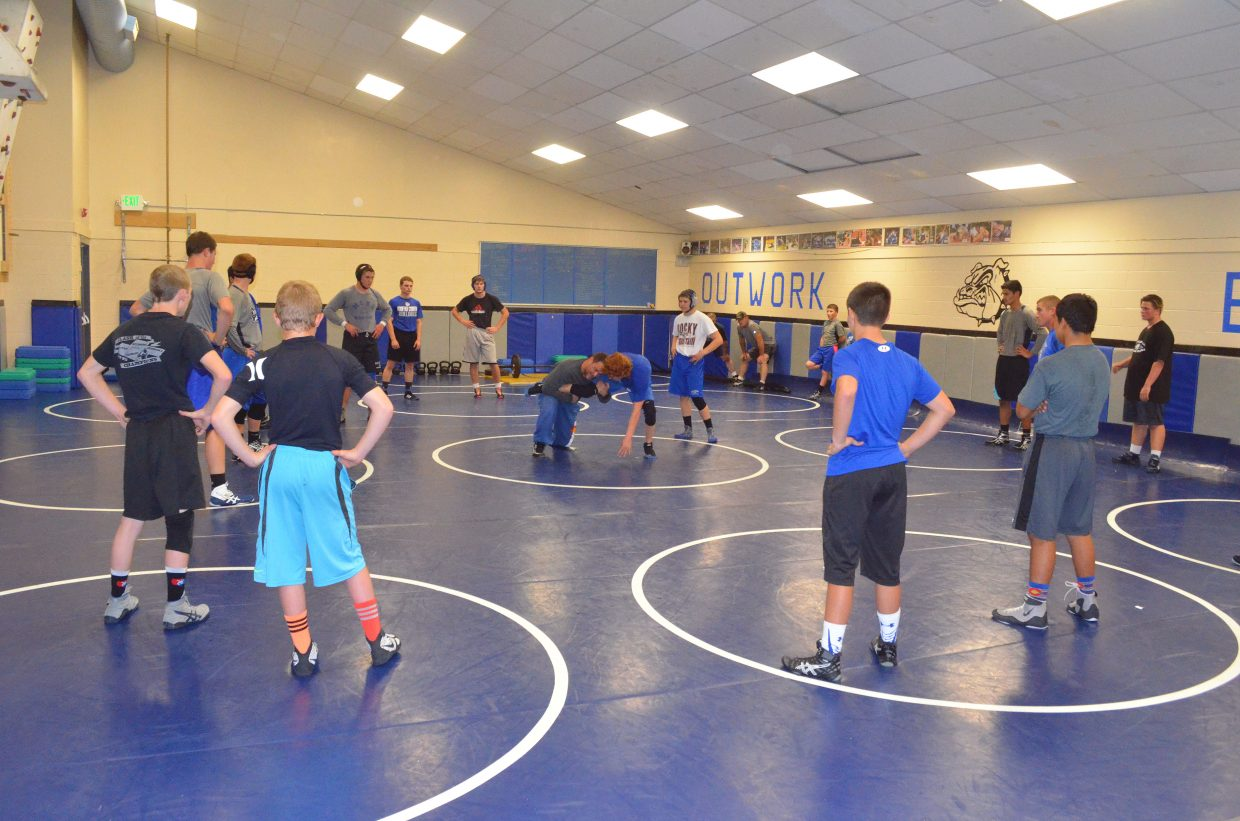 Moffat County High School wrestlers observe as coach Tanner Linsacum and senior Issik Herod demonstrate proper technique during a practice in the wrestling room.
