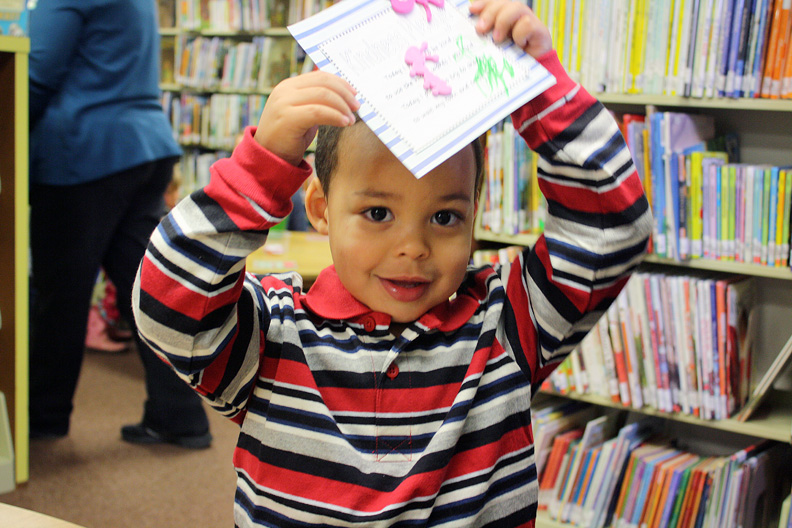 Treavon Wilson, 2, shows off his art work during the crafts segment of story time at the Moffat County Library.