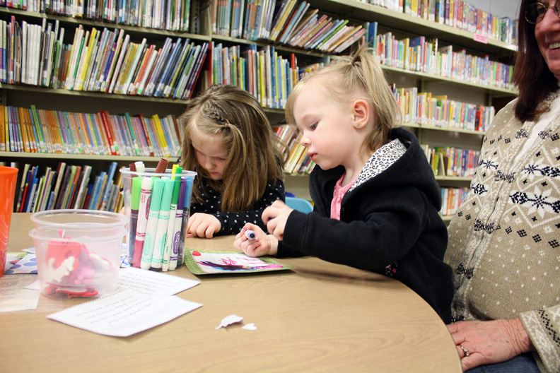 Kali Walton, 4, and Khloe Walton, 2, color together after story time at the Moffat County Library.