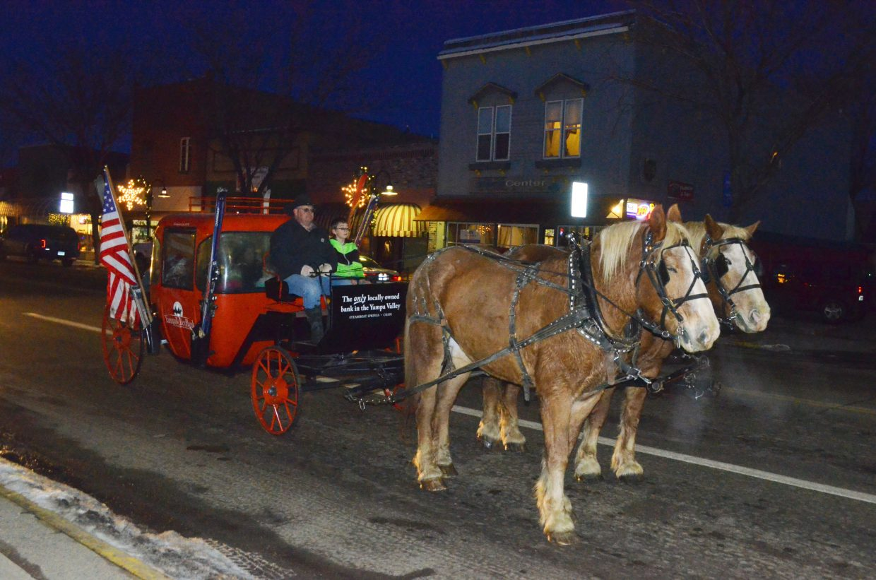 A horse-drawn wagon awaits a green light at the intersection of Yampa Avenue and Victory Way while carting riders during Saturday's Down Home Christmas Celebration.