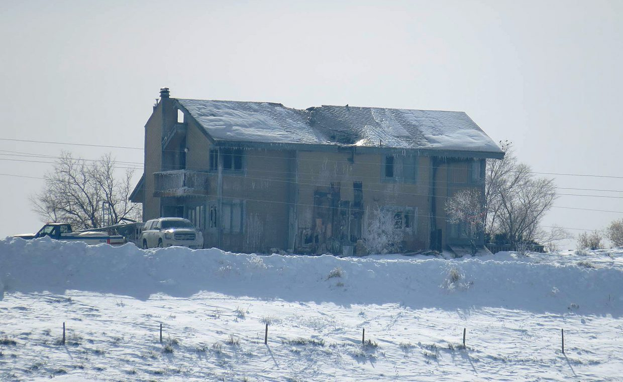 The remains of the home as seen from Columbine Apartments on Sunday.