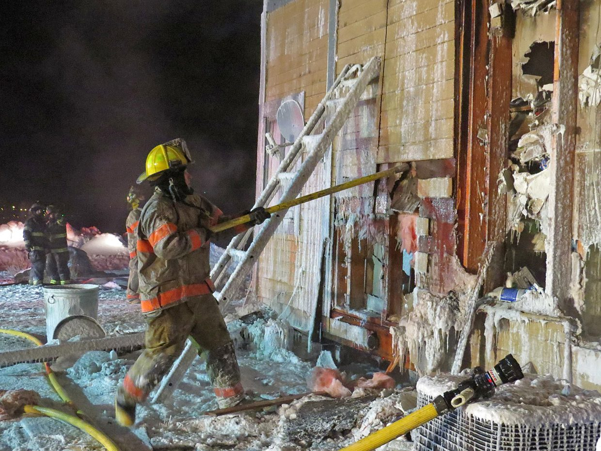 A firefighter rips away at an ice-coated wall.