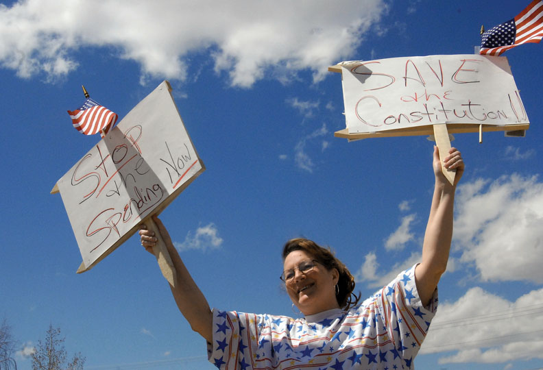 """Lynne Herring, of Craig, holds signs at the Tax Day Tea Party protest Wednesday in front of the Moffat County Courthouse. Herring said she was proud she """"had the right to stand here with a sign and protest the government. Where else in the world can you do that?"""""""