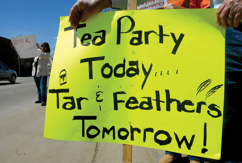 """Jan Lackey, left, of Craig, stands on Victory Way encouraging drivers to """"Honk if You Agree"""" with the Tax Day Tea Party rally. Bill Greenwood holds the sign on the right. More than 200 demonstrators took to the street to protest government taxation as part of a nationwide grass-roots movement. For more photos, see page 8."""