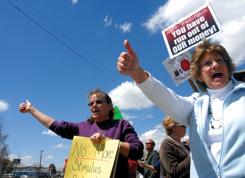 Lorrie Butler, left, and Renee Hamaker call to drivers Wednesday to honk in support of the Tax Day Tea Party protest. Several motorists gave long and repeated honks as they drove down Victory Way.