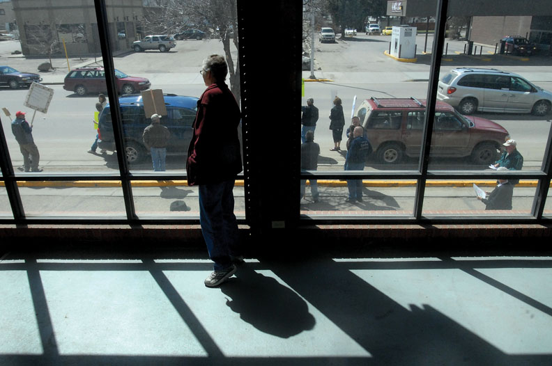 A woman watches protesters gather in front of the Moffat County Courthouse shortly before noon Wednesday, when the rally officially began. Protesters started arriving about 11:30 a.m., and many stayed after the scheduled 1 p.m. finish time.