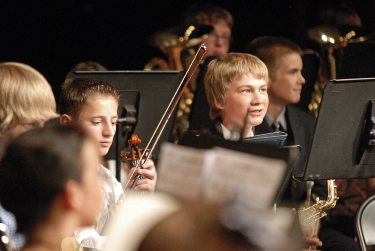 Craig Middle School seventh-graders Jacob Vallem, left, with the violin, and Aaron Lee performed Thursday during a concert at Moffat County High School in honor of CMS band teacher Craig Smith.