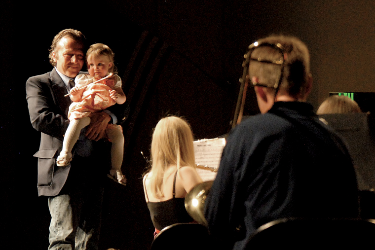 """Deron Smith holds his daughter, Isabella Marie Smith, onstage Thursday at the Moffat County High School auditorium. Deron is the son of the late Craig Middle School band teacher Craig Smith, and Isabella is Craig's granddaughter. Craig Smith, a popular instructor at the middle school, died Sunday. Isabella """"conducted"""" the final song of Thursday's concert, which was a tribute to her grandfather."""