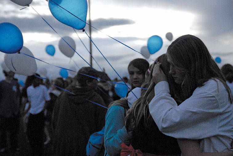 Craig Middle School eighth-grader Trenna Kaiser comforts fellow band members Thursday during a service honoring band teacher Craig Smith, who died Sunday. He was 64. The service took place on the Moffat County High School football field after a CMS band and choir concert at the school's auditorium. Hundreds of blue and white balloons were released from the field at sunset.