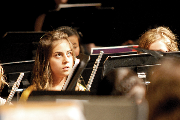 Craig Middle School seventh-grader Stephanie Duarte looks toward conductor John Bolton on the stage of the Moffat County High School auditorium. The event was originally put together by CMS band teacher Craig Smith as a spring concert. However, when Smith died on Sunday, Bolton took the baton and conducted the concert as a memorial.