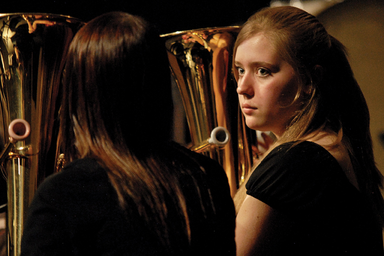 Craig Middle School eighth-grader Treann Quick, right, shares a moment with fellow baritone player Brynnae Dempster on Thursday on stage at the Moffat County High School auditorium.