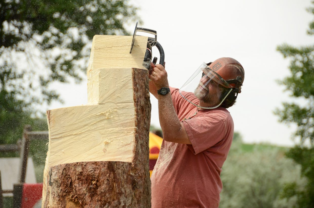 Robert Waits carves out chunks of his tree with a chainsaw Wednesday morning at Loudy Simpson Park. Waits, of Lander, Wyo., is one of 11 artists competing in the 14th annual Whittle the Wood competition this year in Craig.