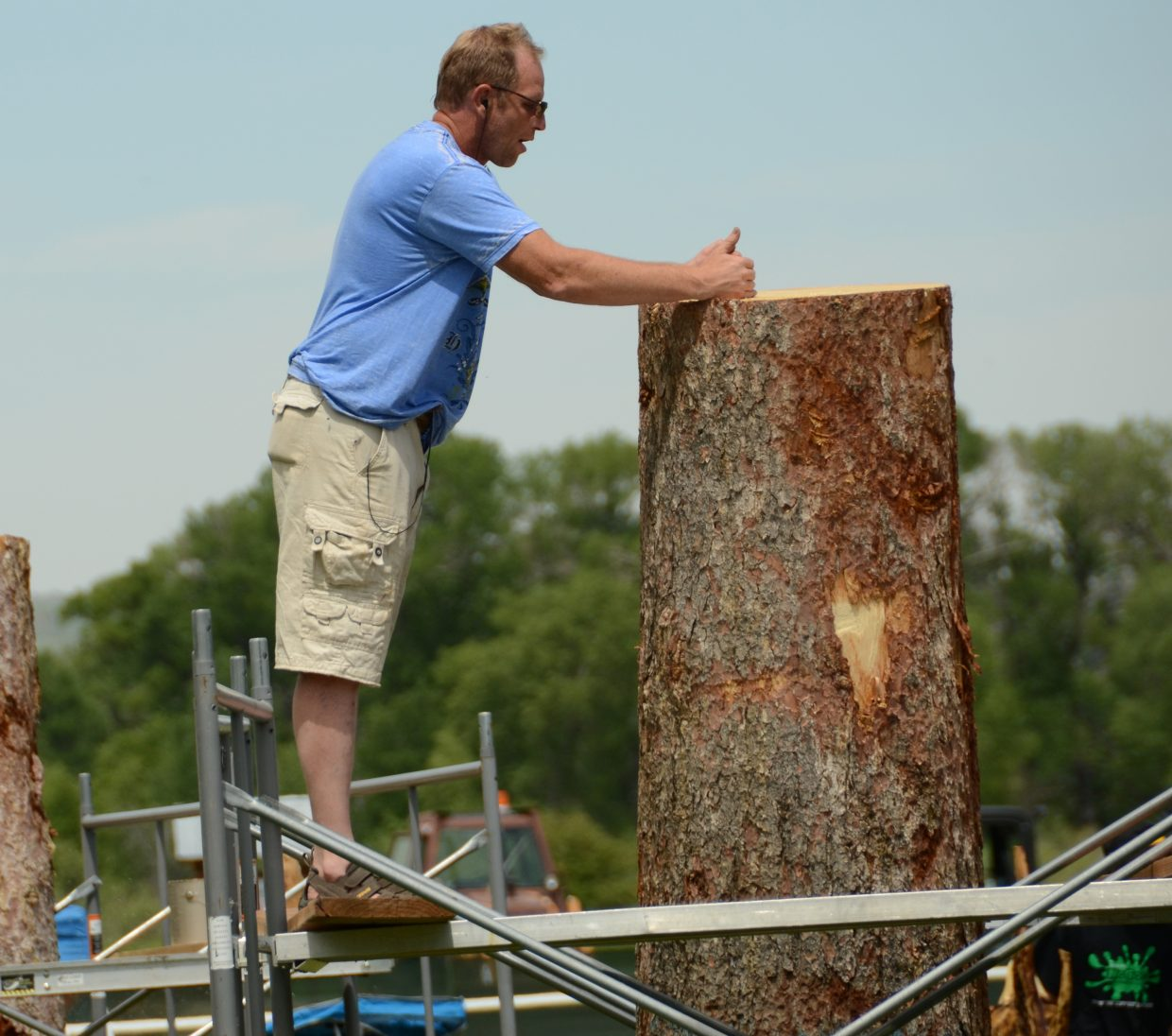 Ron Eye, of Vernal, Utah, envisions what he needs to do with his tree trunk before cutting into it Wednesday morning at Loudy Simpson Park.