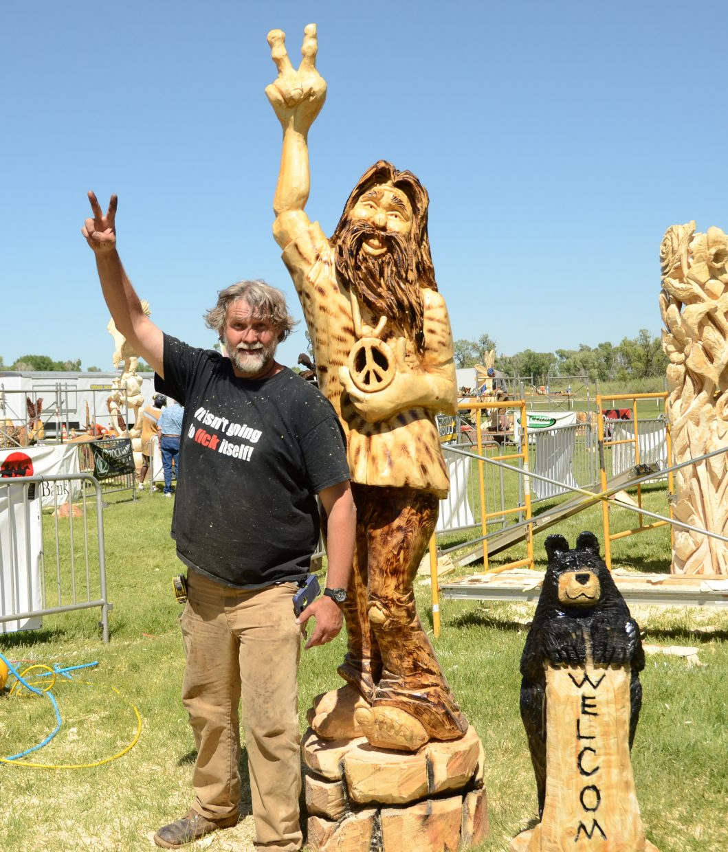 Robert Waits poses with his finished hippie carving Friday afternoon at Loudy-Simpson Park.