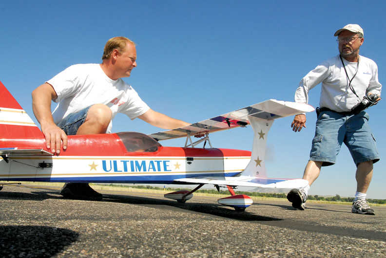 Charlie Williams holds a remote control Ultimate biplane while Mike Grable spins the propeller to start it Saturday at the Craig Centennial AirFest.