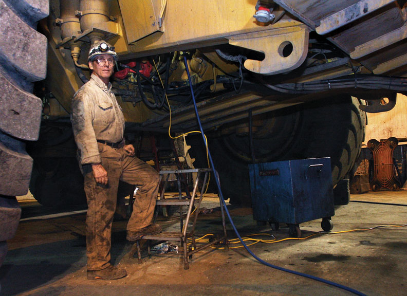 Pat Byers takes a moment from working on a Caterpillar haul truck for a photo Thursday at the Colowyo Coal Co. maintenance shop. Byers, a heavy equipment mechanic, has worked at the mine for about 20 years.