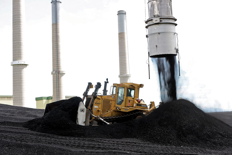 A bulldozer, driven by Tom Whiffen, pushes coal away from a stackout conveyor Thursday at Tri-State Generation and Transmission's Craig Station's east stackout. The plant has two stacks to keep coal from Colowyo and Trapper mines separated.