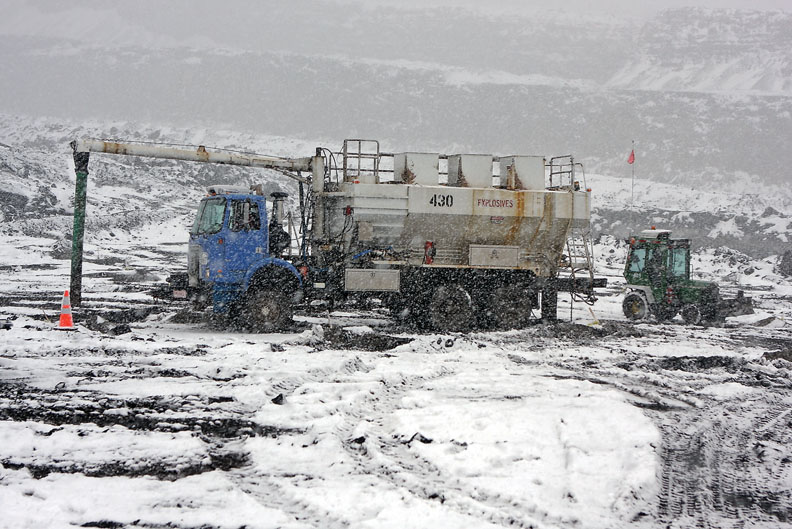 A bulk truck driver on the Colowyo Coal Co., blast crew fills holes with explosives while a small bulldozer stems the holes on a snowy day, May 12, at the mine.
