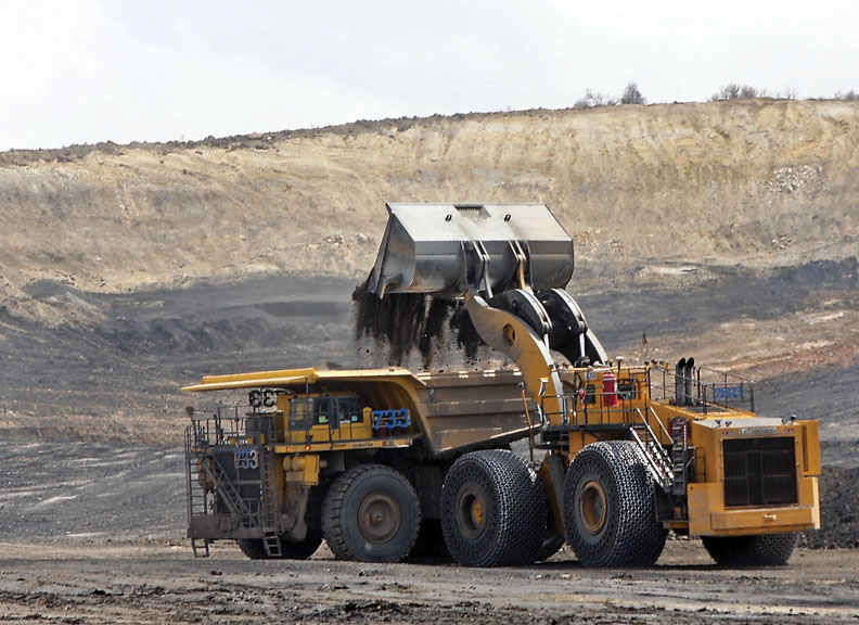 A LeTourneau Technologies front-end loader drops dirt and rock overburden into a Kamatsu haul truck May 14 at the Trapper Mining Co. The loader is the largest on the market and can fill the 240-ton haul truck in about four scoops.