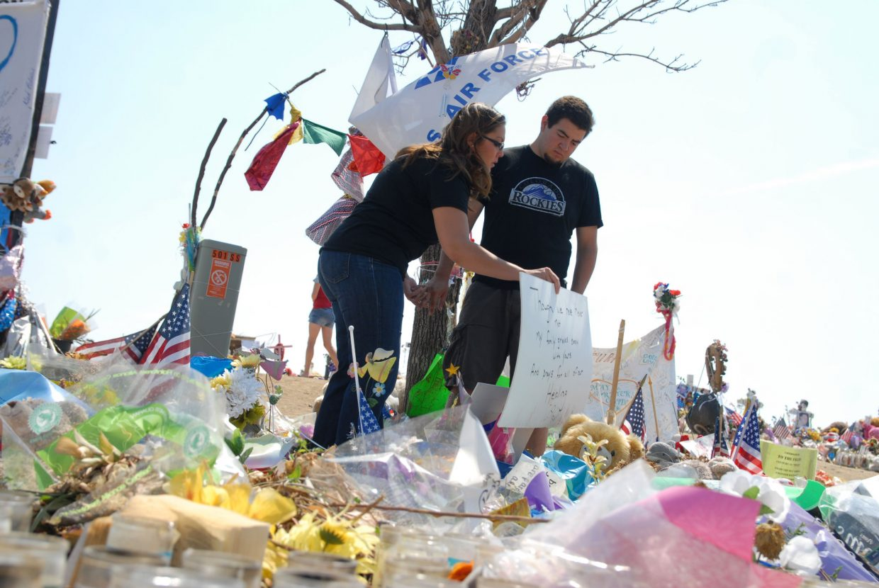 """Jacque Archuleta, 24, a Craig native and Englewood resident, and her boyfriend, Alex Espinoza, visit memorials Friday near the Century Aurora 16 multiplex, the scene of one of the worst shootings in U.S. history. The couple was in theater 9 when a gunman opened fire during a midnight screening of """"The Dark Knight Rises."""""""