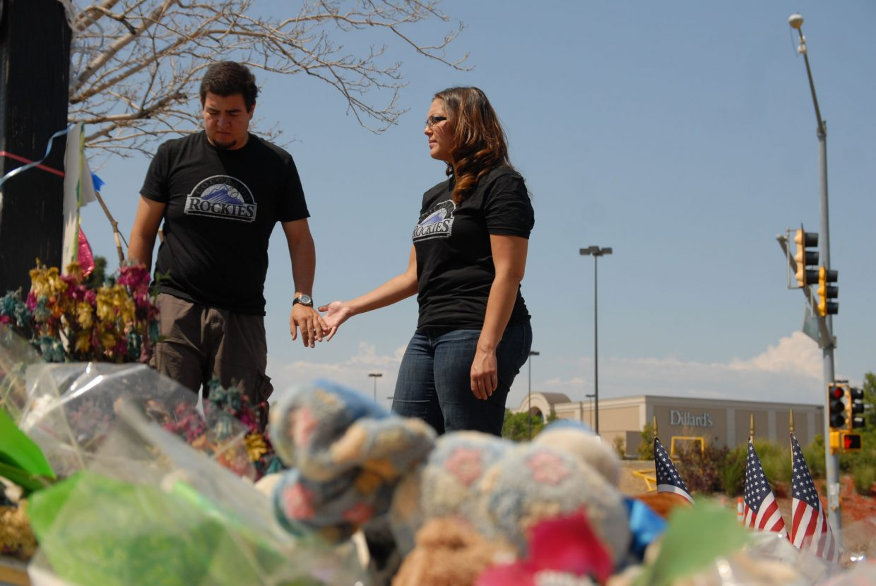 Alex Espinoza and Jacque Archuleta pay their respects Friday to the 12 people killed and 58 wounded in the July 20 shooting at Century Aurora 16. The couple also participated in a vigil at the memorial in the days following the shooting.