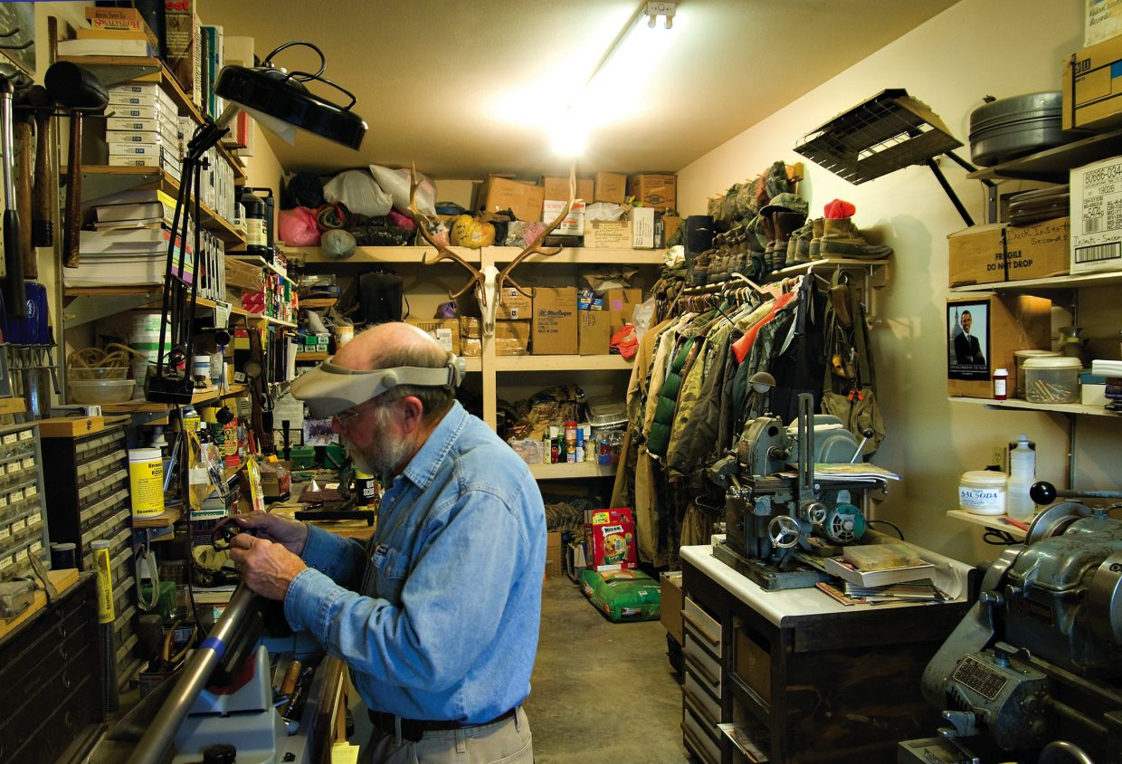 John Kelley works on attaching rings and bases for a scope on a rifle Tuesday at his home in Meeker.