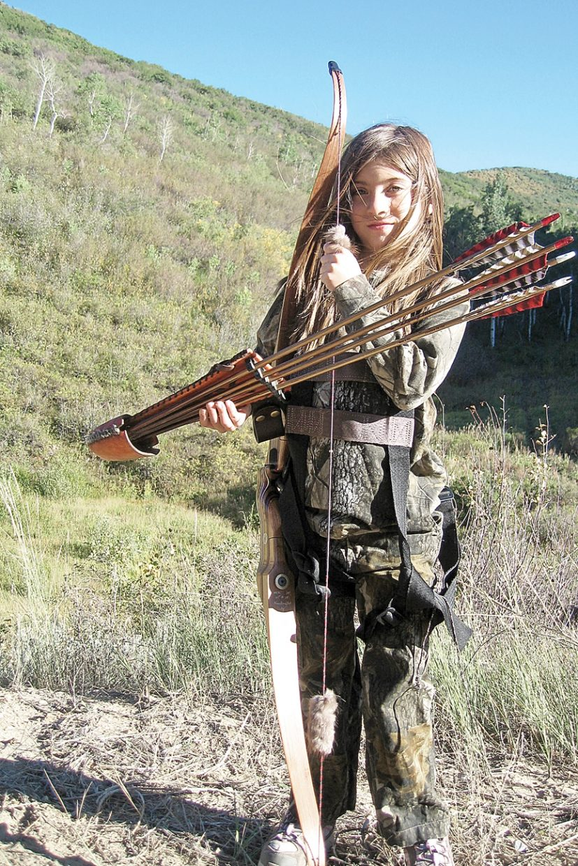 Tiana Nichols, 8, stands with her archery gear during the 2010 archery elk season in Moffat County. Tiana is too young to purchase an elk tag, but she accompanies her father on nearly all of his hunts. She said she can't wait until she's 12, so she can harvest her first elk.