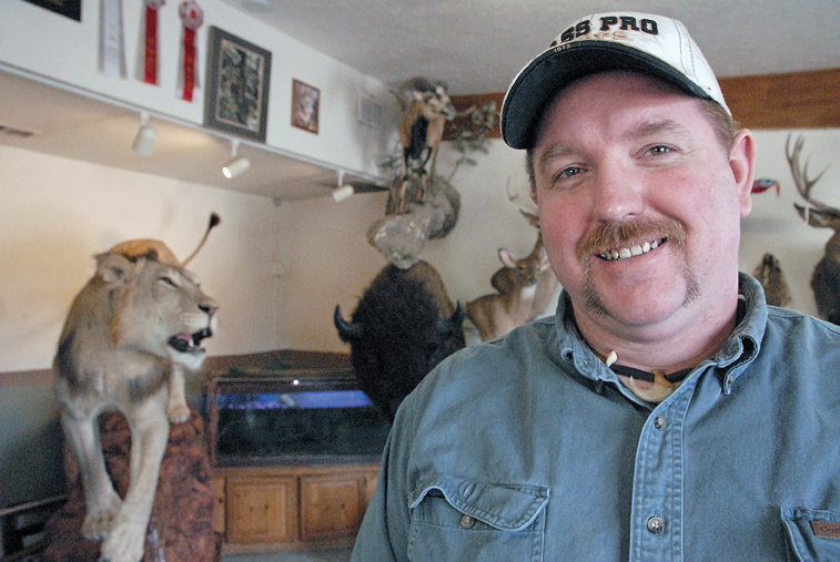 """Craig taxidermist Scott Moore stands in June next to the prize-winning piece """"Can't Kill the King,"""" which he created with taxidermist Leland Reinier. The two men won first place for collective artist at the Colorado State Taxidermy Competition in June in Salida. The piece, which features an African lion, is on display at Moore's business, Mountain Man Taxidermy in Craig."""