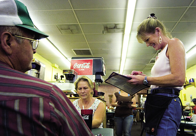 Ted Smythe, left, and his wife, Linda, center, order supper from server Kristi DiMarco at the Base Camp Cafe in Rifle on June 20. According to DiMarco, businesses of all kinds are prospering because of the recent explosion of oil and gas exploration in the Rifle area.