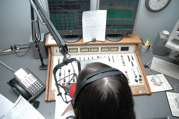 Carmel Schiff reads the news during the noon hour on Tuesday in the 55 Country studio. Schiff is one of three employees who helps track down news.