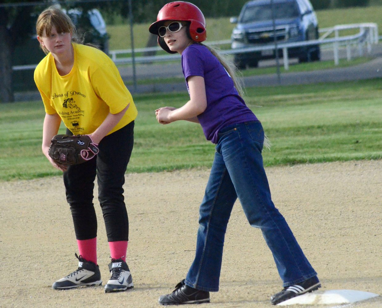 Arena of Dreams' Dylan Herndon, left, keeps an eye on runner Reagen Bower, of A Kidz Dentist, during a tournament game for Craig Parks and Recreation softball.