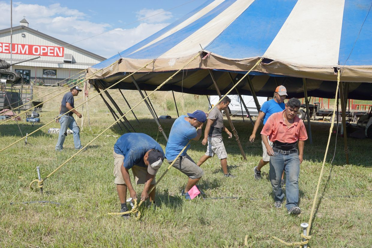 The tent crew works as a team to push the push-pole style big top into place and tie it off.