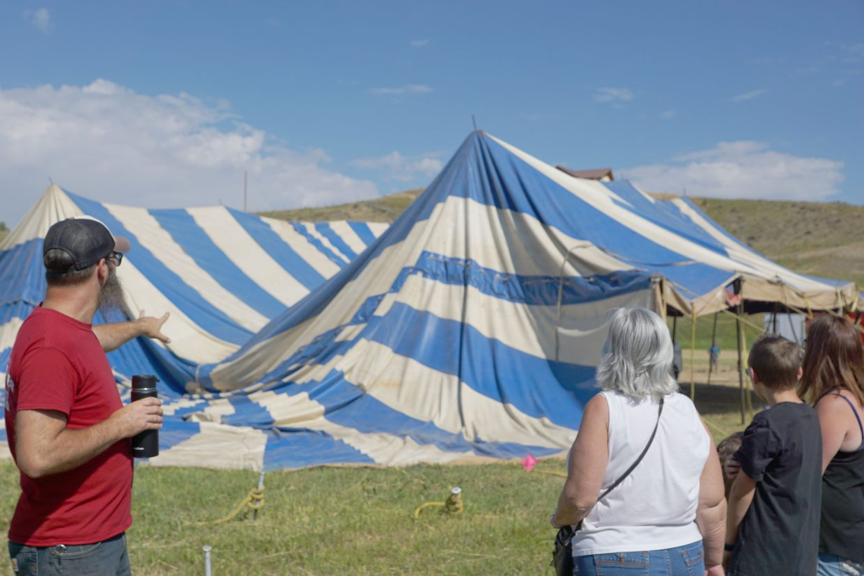 Tour guide and circus clown, Leo Acton, left, explains the tent raising process to a small crowd.