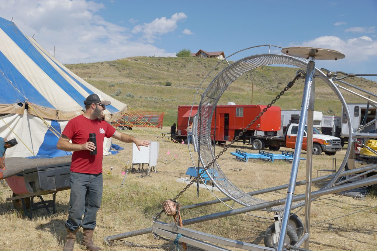 As the tent crew works to get the walls of the tent in place, performers begin moving equipment into place. The