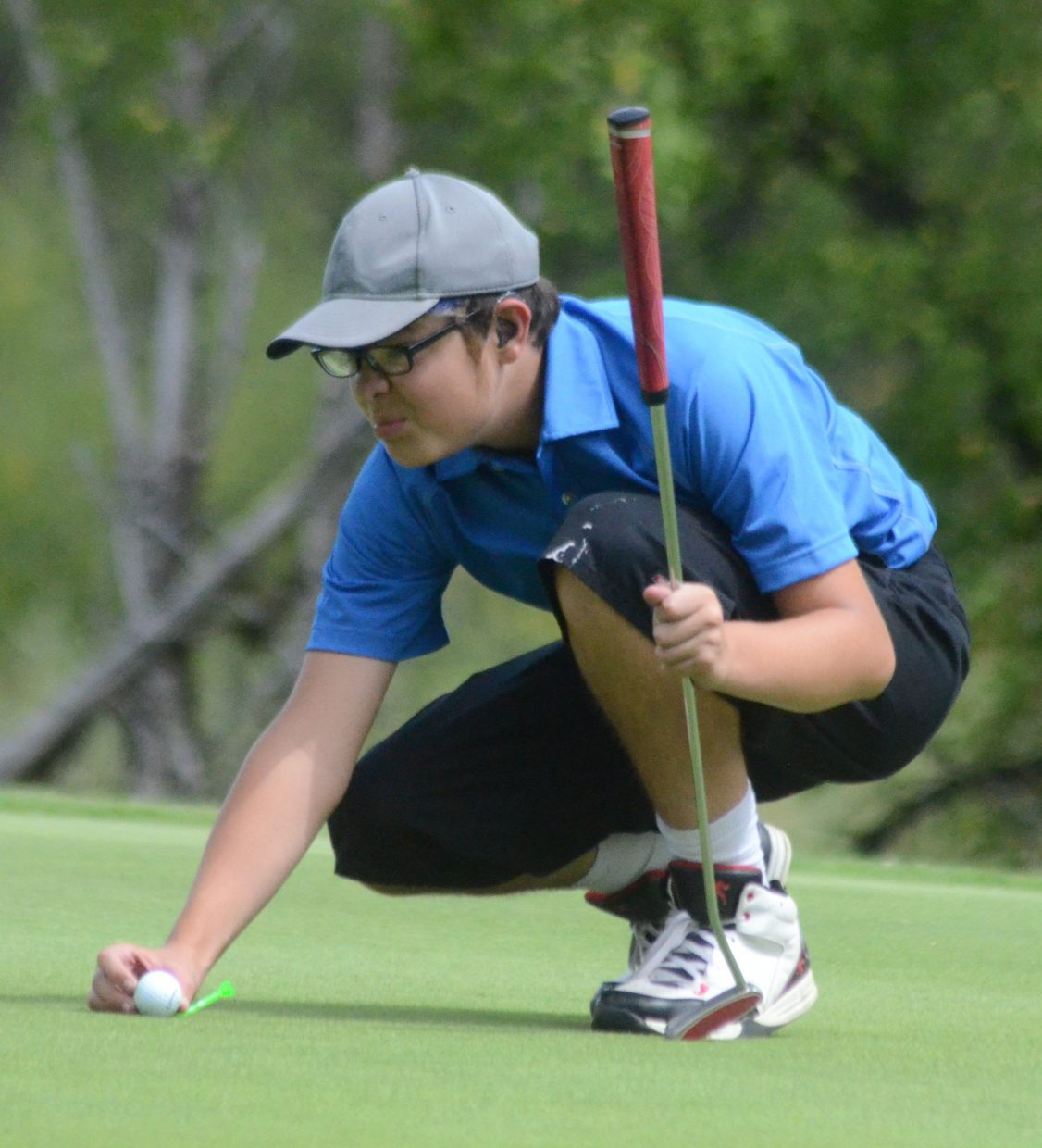 Moffat County High School's James DeWald checks his ball placement on the eighth green at Yampa Valley Golf Course during Wednesday's Bulldog Invitational.