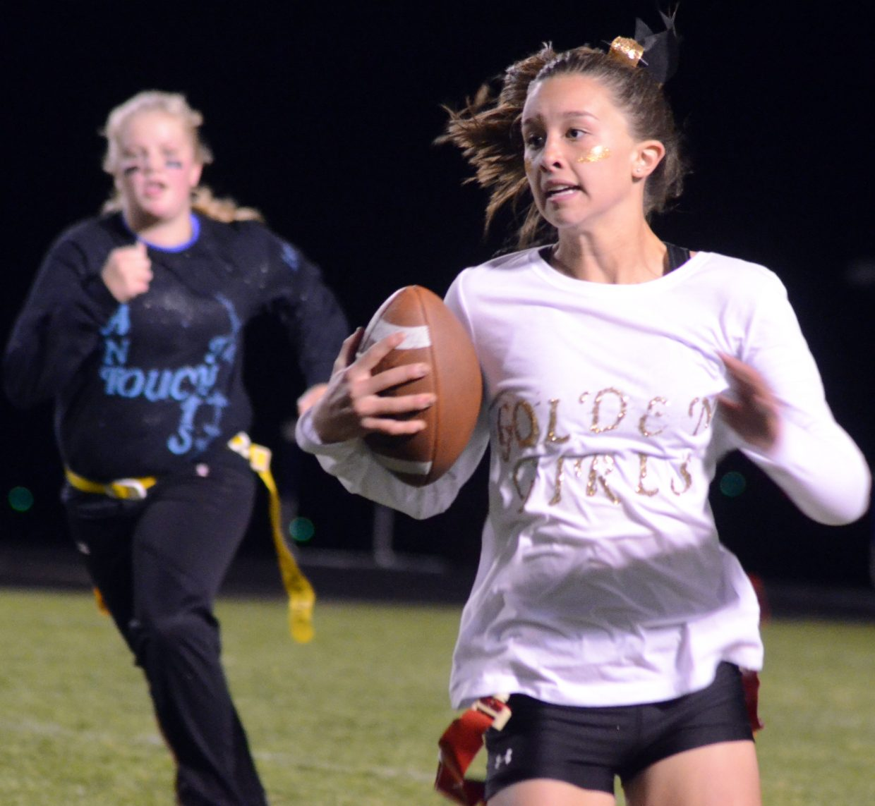 Golden Girls' Emaleigh Papierski gains yardage during the Powder Puff Football tournament Wednesday night at Moffat County High School.