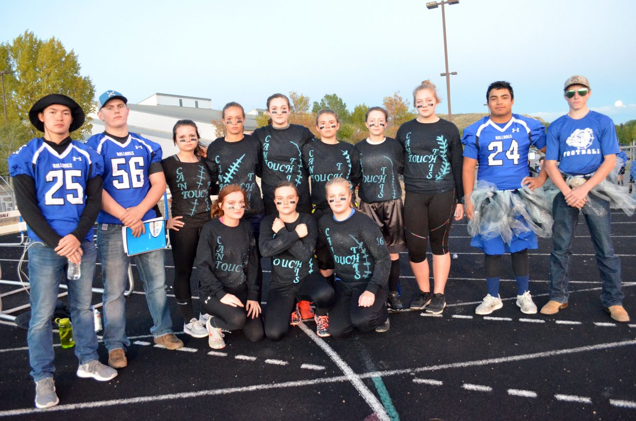 The players and coaches of Can't Touch This gather leading up to games for the Powder Puff Football tournament Wednesday night at Moffat County High School.