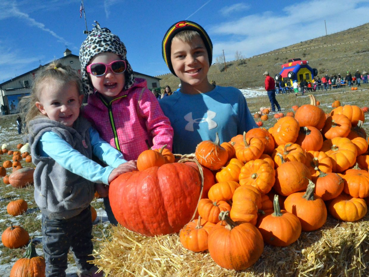 From left, Paisley White, Addy Chamberlain and Keegan Herod pose with a pile of pumpkins at the Wyman Living History Museum's pumpkin patch Sunday.