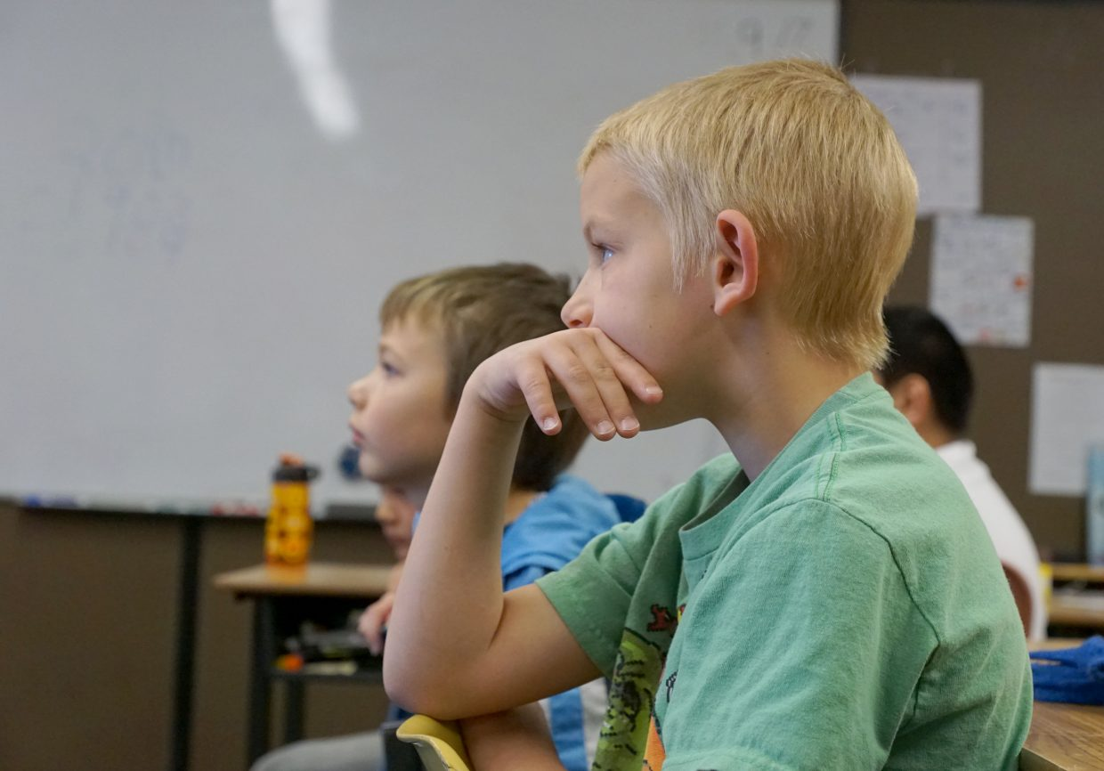 Third-grade students Chance Green, front, and Morrigen Miller, back, listen attentively during Mayor John Ponikvar's presentation to Bobbie McAlexander's third-grade class at East Elementary School.