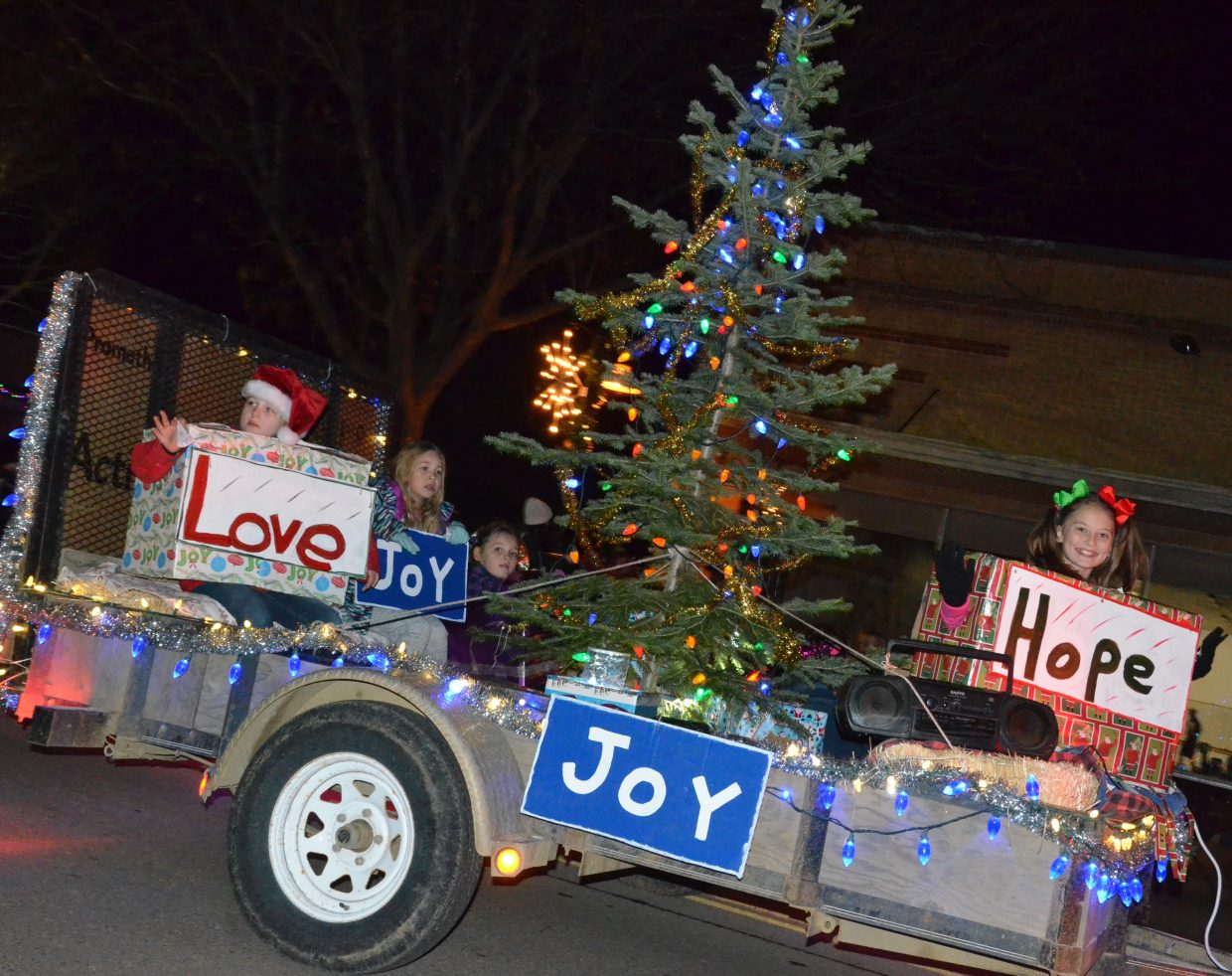 Craig Girl Scouts personify yuletide gifts of love, hope and joy atop their float entry in Saturday's Parade of Lights.