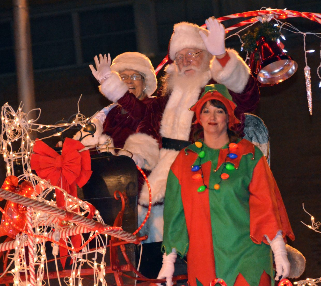 Santa Claus, Mrs. Claus and helpers wave from the final float of the night during Saturday's Parade of Lights.