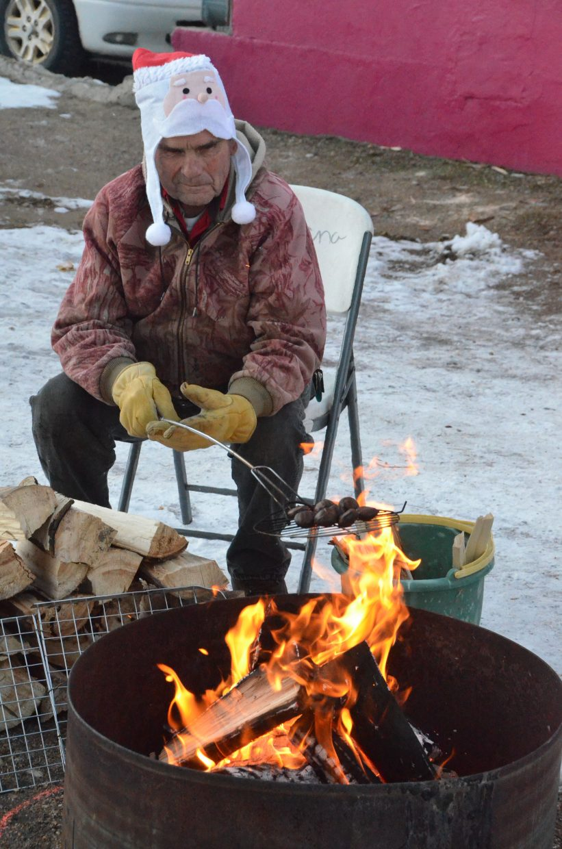 Neil Folks roasts a bundle of chestnuts over an open flame in Alice Pleasant Park during Saturday's Down Home Christmas Celebration.