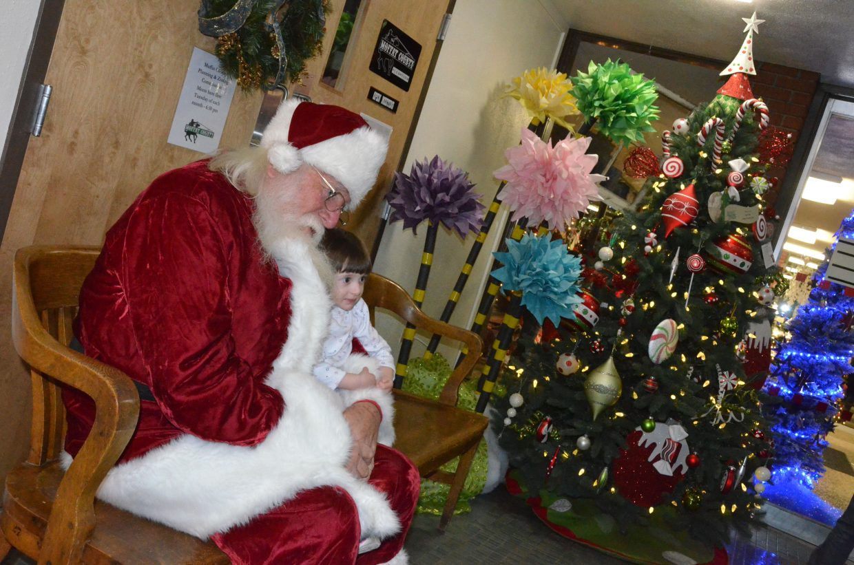Aly Bergstrom, 2, cuddles up with Santa Claus at the Festival of Trees at Moffat County Courthouse.