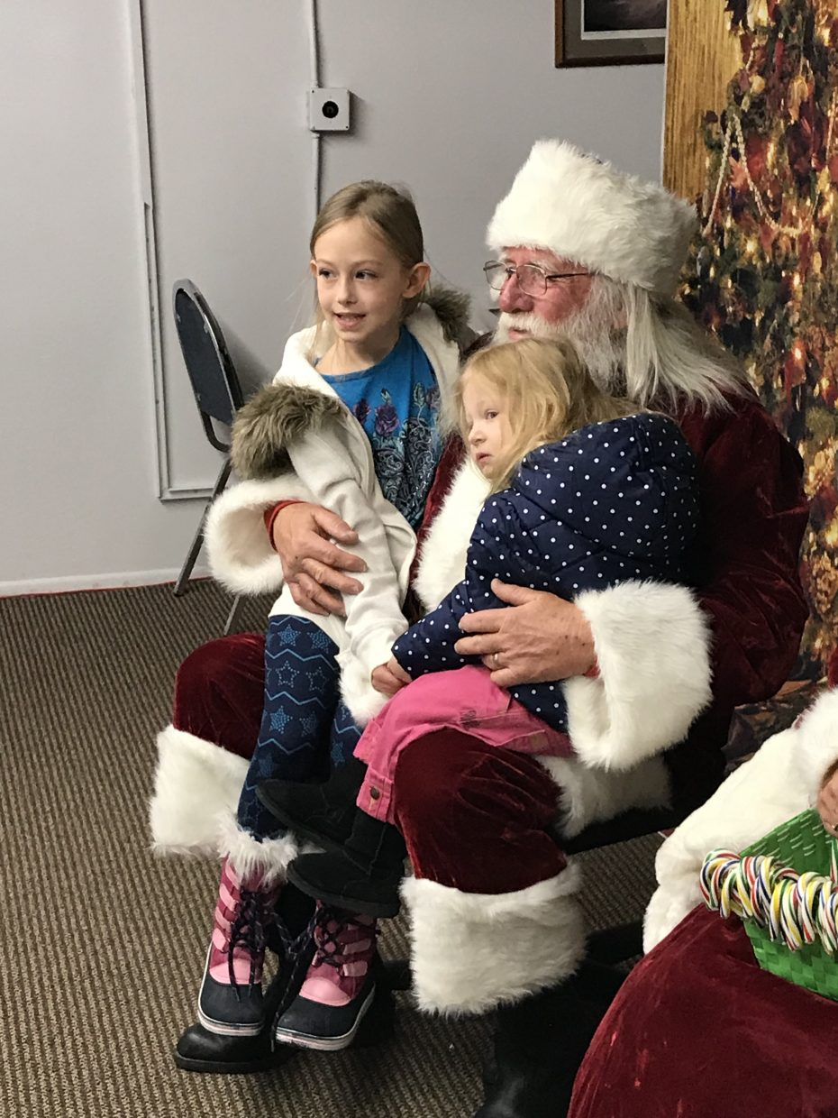 Santa Claus greets two young visitors at the annual Letters to Santa event, held Wednesday at the Craig Press.