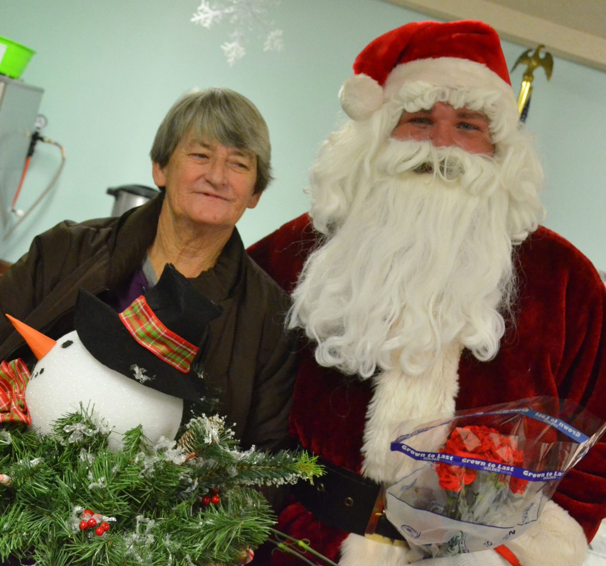 Lisa Friend is joined by Santa Claus during the Sunset Meadows Christmas party Wednesday.